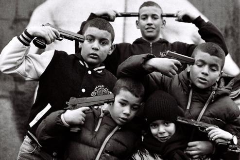 Enfants jouant avec des armes factices, simulant le suicide collectif, devant l'oeuvre de Bandian.